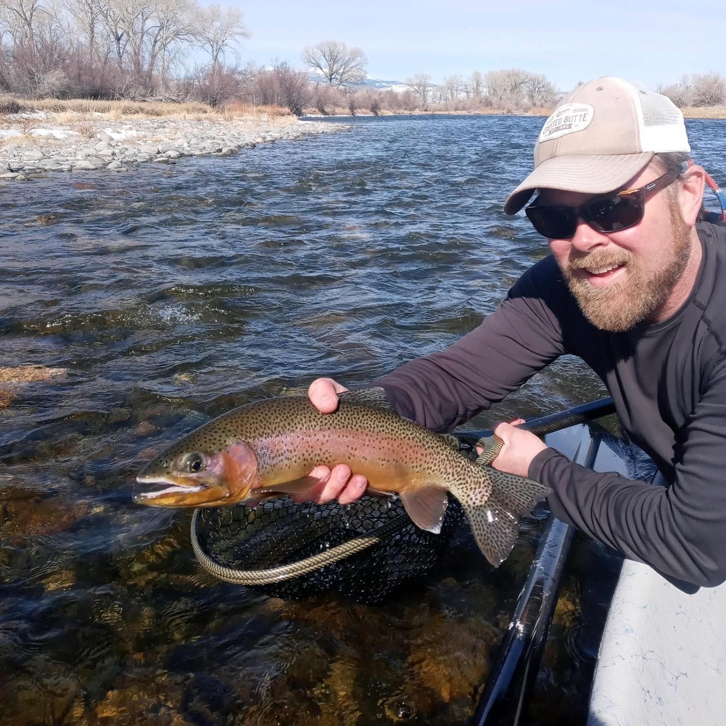Fishtales Outfitting guide Dave Hernden holding up a beautiful Madison river rainbow trout.