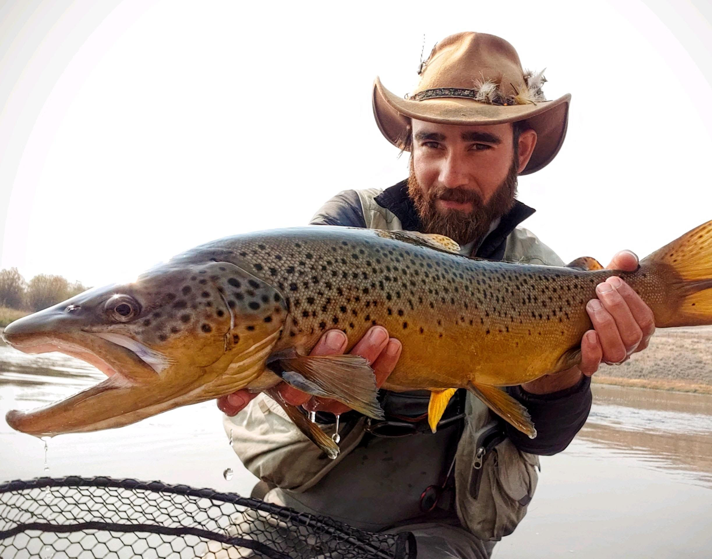 Fishtales Outfitiin guide Wade Whitaker holding a monster brown trout.